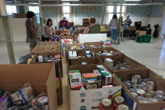 FCCMP staff sorting and creating grocery bags of food