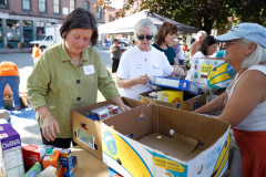Sen. Jo Comerford, left, sorts through food donations with volunteers during the 15th annual Fill the Belly Bus Community Food Drive on Friday afternoon at the Greenfield Common.